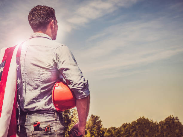 Handsome man with tools, holding an American Flag stock photo