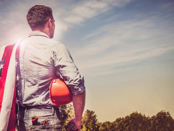 homem considerável com ferramentas, prendendo uma bandeira americana - dia do trabalhador - fotografias e filmes do acervo