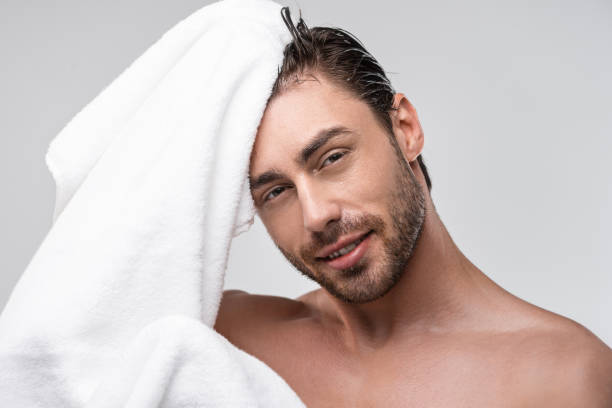 handsome man with towel handsome man with wet hair and towel, isolated on grey wet hair stock pictures, royalty-free photos & images