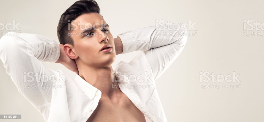 Handsome man with trendy hairstyle dressed in a unbuttoned white shirt. stock photo