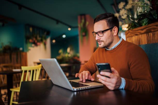Hombre guapo trabajando en la computadora portátil y el uso de teléfono inteligente, copiar el espacio. - foto de stock