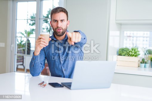 Handsome man working using computer laptop and drinking a cup of coffee pointing with finger to the camera and to you, hand sign, positive and confident gesture from the front