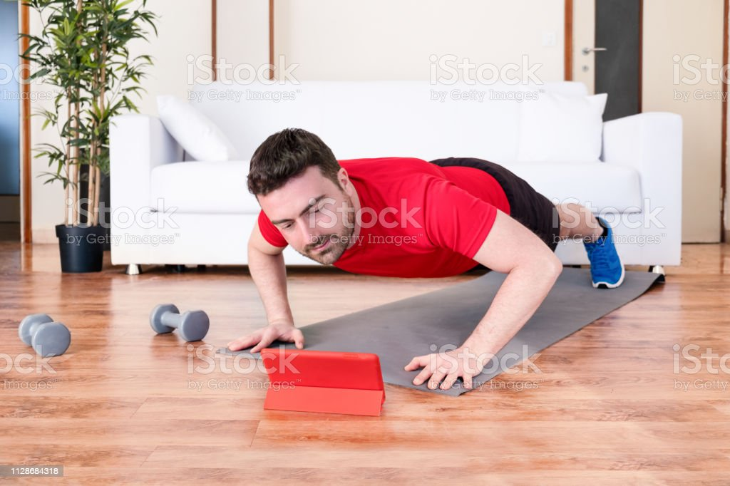 Handsome man workout with push ups at home stock photo