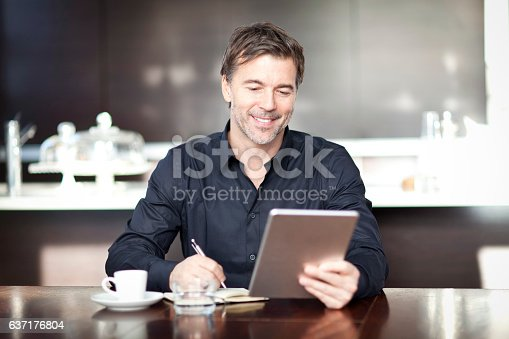 istock Handsome Man Writing At The Coffee Shop. Using Computer. 637176804