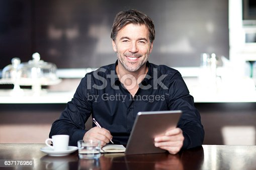 istock Handsome Man Writing At The Coffee Shop. Using Computer. 637176986