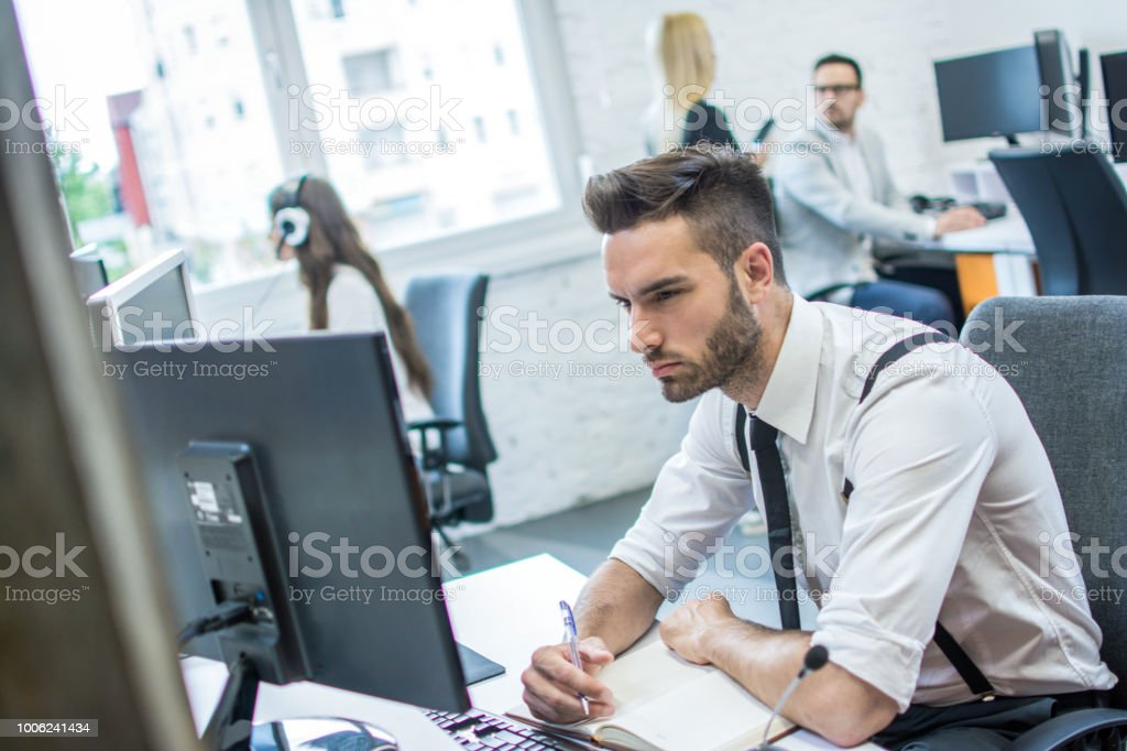 Handsome man writing notes on a writing pad while sitting at his desk...