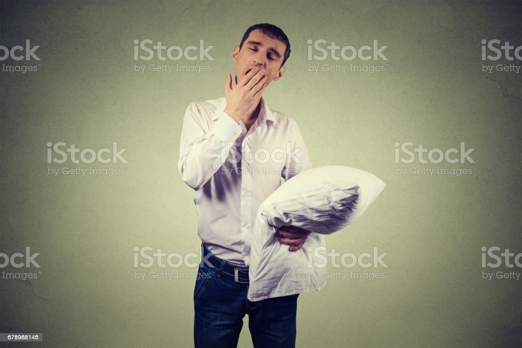 Handsome man yawning with a pillow in hand. Sleep deprivation, burnout, laziness concept photo libre de droits