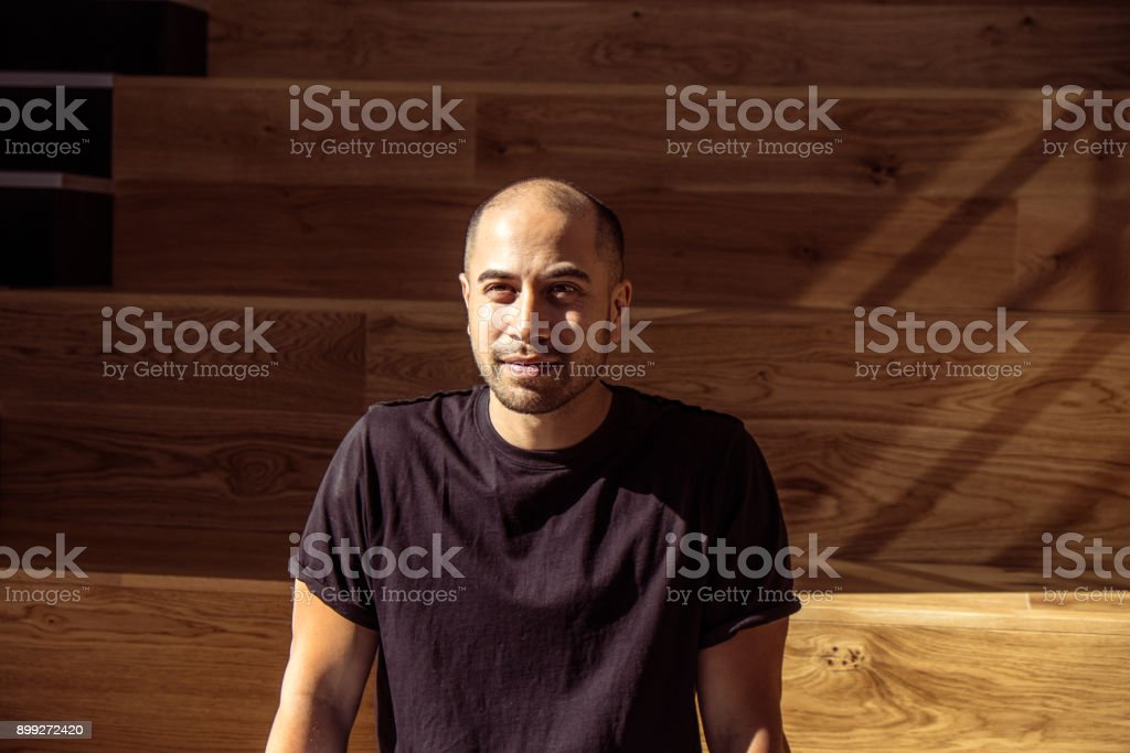 Handsome Maori Caucasian male in black t-shirt sitting on interior steps of work place looking happy stock photo
