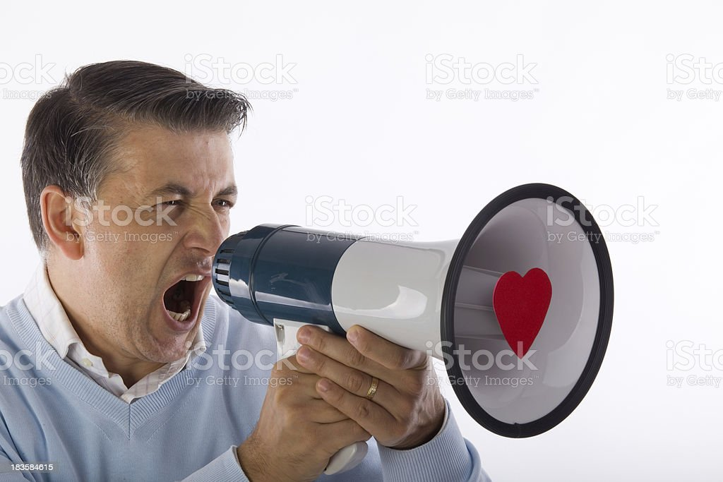 Handsome mature adult man shouting on heart shaped megaphone royalty-free stock photo