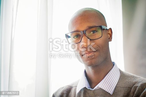 istock Handsome mature black male bald intellectual portrait by window 611882512