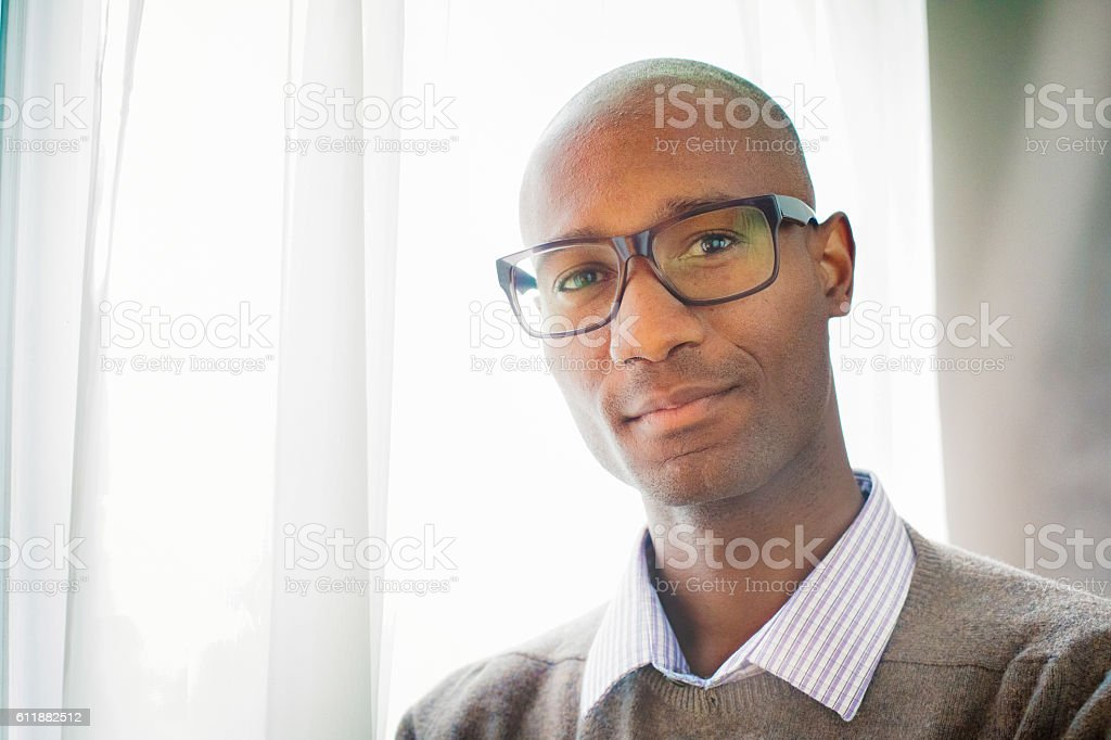 Handsome mature black male bald intellectual portrait by window stock photo