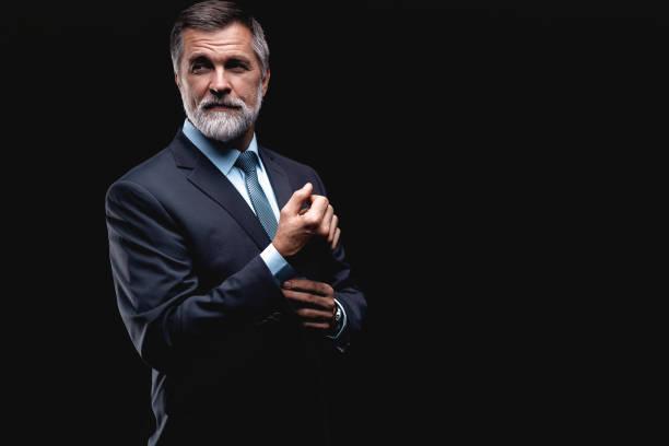 hombre de negocios maduro guapo aislado sobre fondo negro - bien parecido fotografías e imágenes de stock