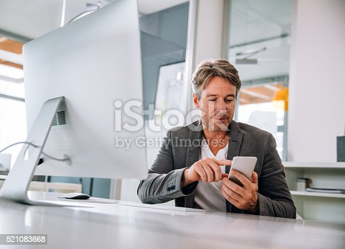 513583458 istock photo Handsome mature executive smiling at text on his smartphone 521083668