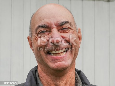 istock Handsome mature happy bald man smiling at the camera 1186469670