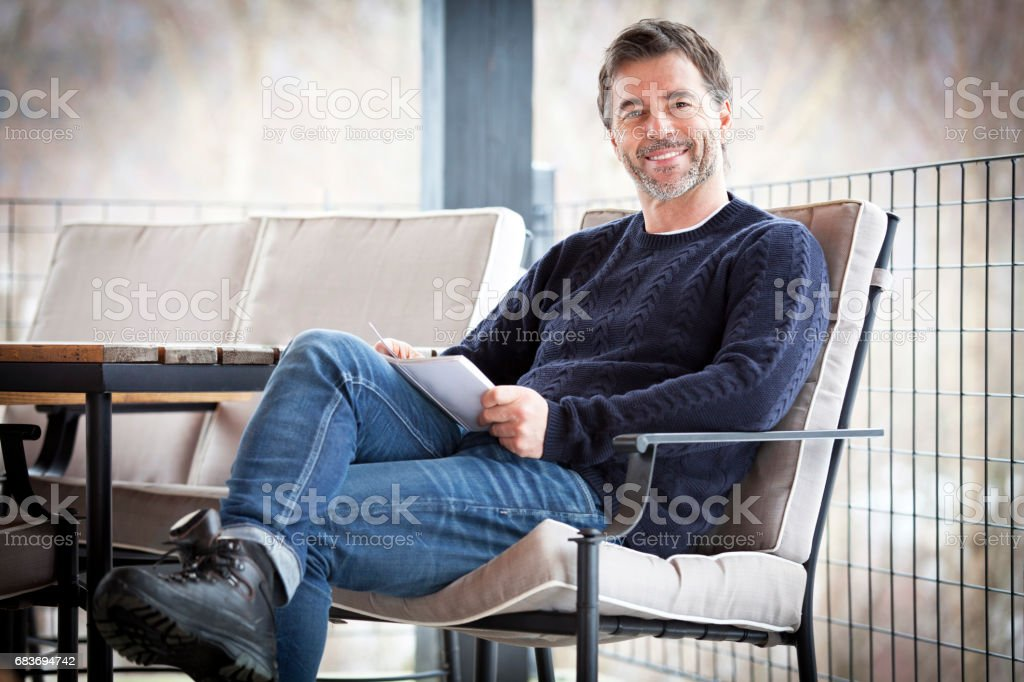 Handsome Mature Happy Man Smiling At The Camera.Outside. Reading a book Lizenzfreies stock-foto