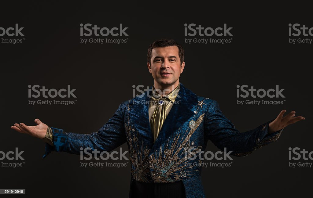Handsome mature illusionist or wizard or magician conjuring stock photo