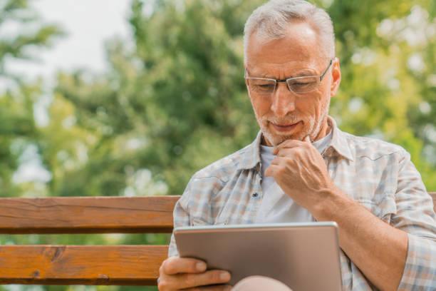 잘 생긴 성숙한 남자 에 안경 사용 디지털 태블릿 에 벤치 에 공원 - 디지털 태블릿 사용하기 뉴스 사진 이미지