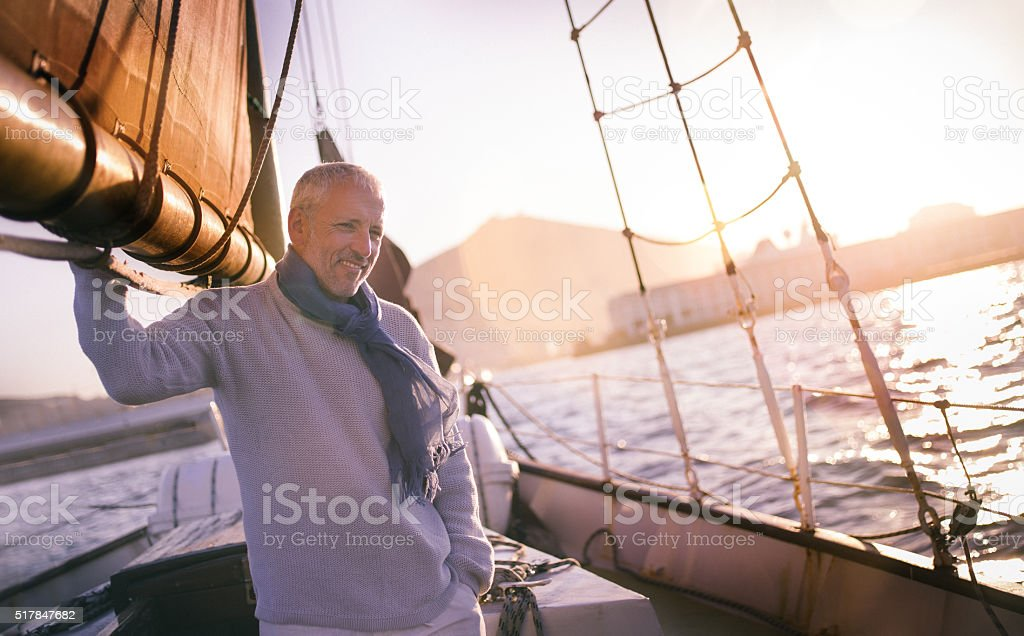 Handsome Mature man on yacht in picturesque sunset stock photo