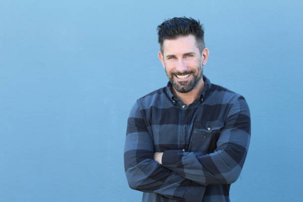 Handsome mature man smiling and laughing Handsome mature man smiling and laughing while crossing his arms with copy space. plaid shirt stock pictures, royalty-free photos & images