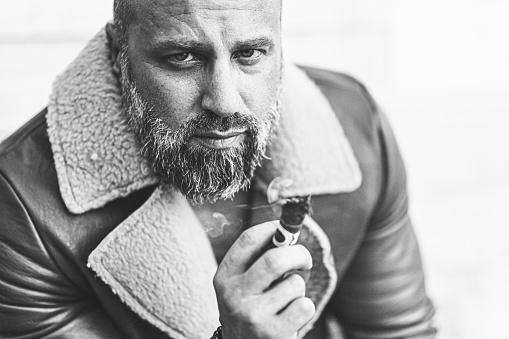 Handsome guy with beard smoking cigar