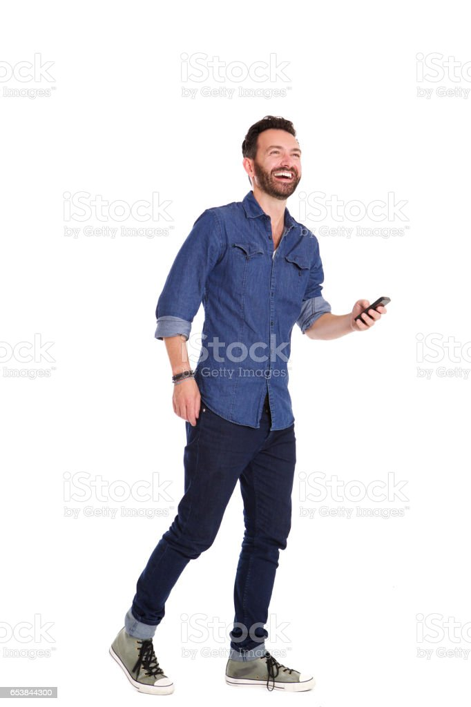 Handsome mature man walking with mobile phone and laughing stock photo