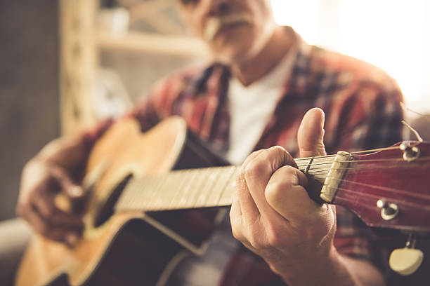 handsome mature man with guitar - hobby's stockfoto's en -beelden