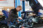 istock Handsome mechanic in uniform is working in auto service garage. Repair service. 1189373314