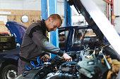 istock Handsome mechanic in uniform is working in auto service garage. Repair service. 1189374054