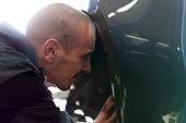 istock Handsome mechanic in uniform is working in auto service garage. Repair service. 1189376756