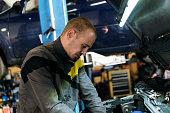 istock Handsome mechanic in uniform is working in auto service garage. Repair service. 1189377251