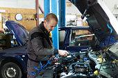 istock Handsome mechanic in uniform is working in auto service garage. Repair service. 1189377267