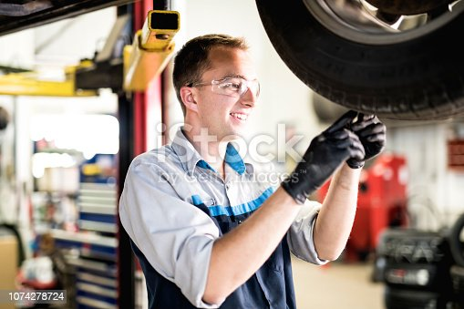istock Handsome mechanic job in uniform working on car check tire wear 1074278724