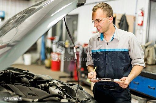 istock Handsome mechanic job in uniform working on car 1074278828