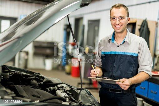 istock Handsome mechanic job in uniform working on car 1074278864