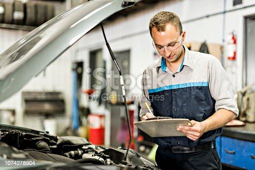 istock Handsome mechanic job in uniform working on car 1074278904