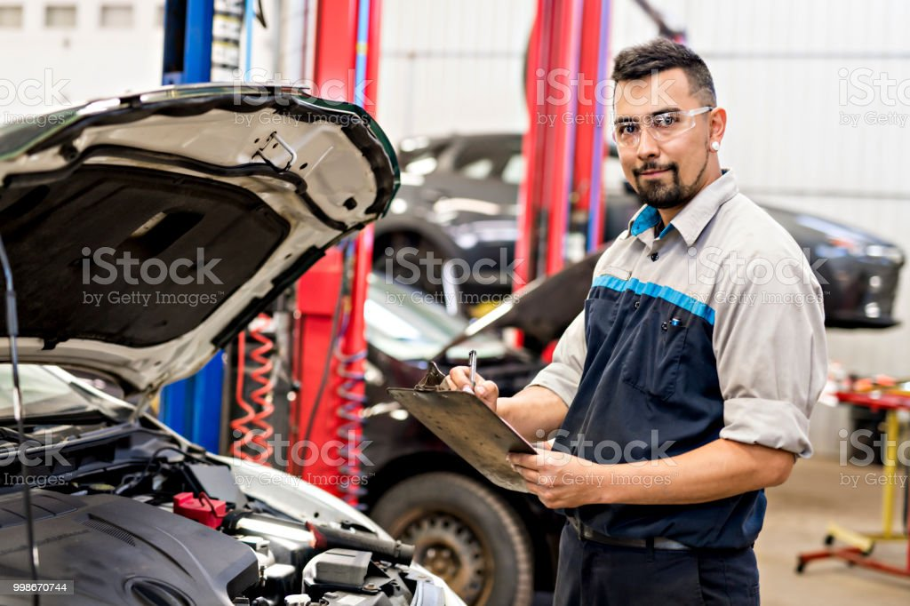 Handsome mechanic job in uniform working on car stock photo