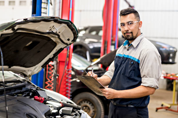 Handsome mechanic job in uniform working on car A Handsome mechanic job in uniform working on car repairman stock pictures, royalty-free photos & images