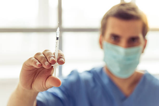 Handsome medical doctor Handsome doctor in blue medical wear and mask is holding a syringe and looking at camera. Hand with syringe in focus tranquilizing stock pictures, royalty-free photos & images