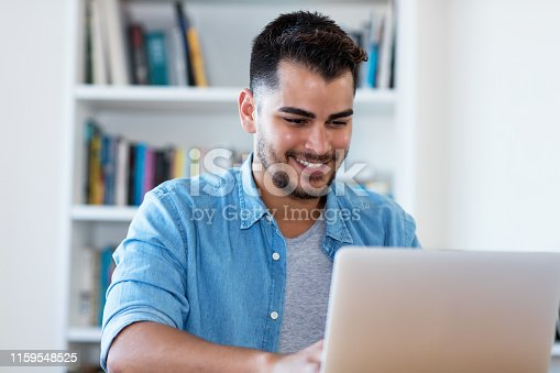 1127582480istockphoto Handsome mexican hipster man at work with laptop 1159548525