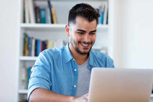 istock Handsome mexican hipster man at work with laptop 1159548525