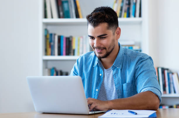 Handsome mexican hipster man sending email with laptop Handsome mexican hipster man sending email with laptop man on computer stock pictures, royalty-free photos & images