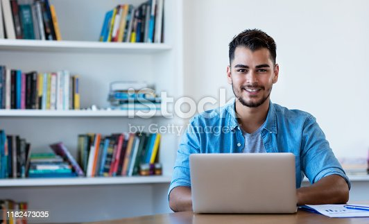 1127582480istockphoto Handsome mexican hipster man working with computer 1182473035