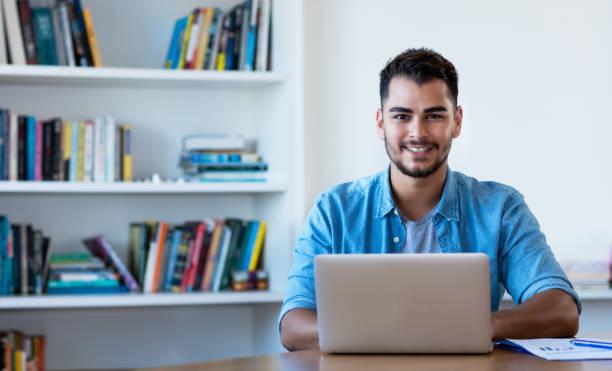 Guapo hombre hipster mexicano trabajando con la computadora - foto de stock