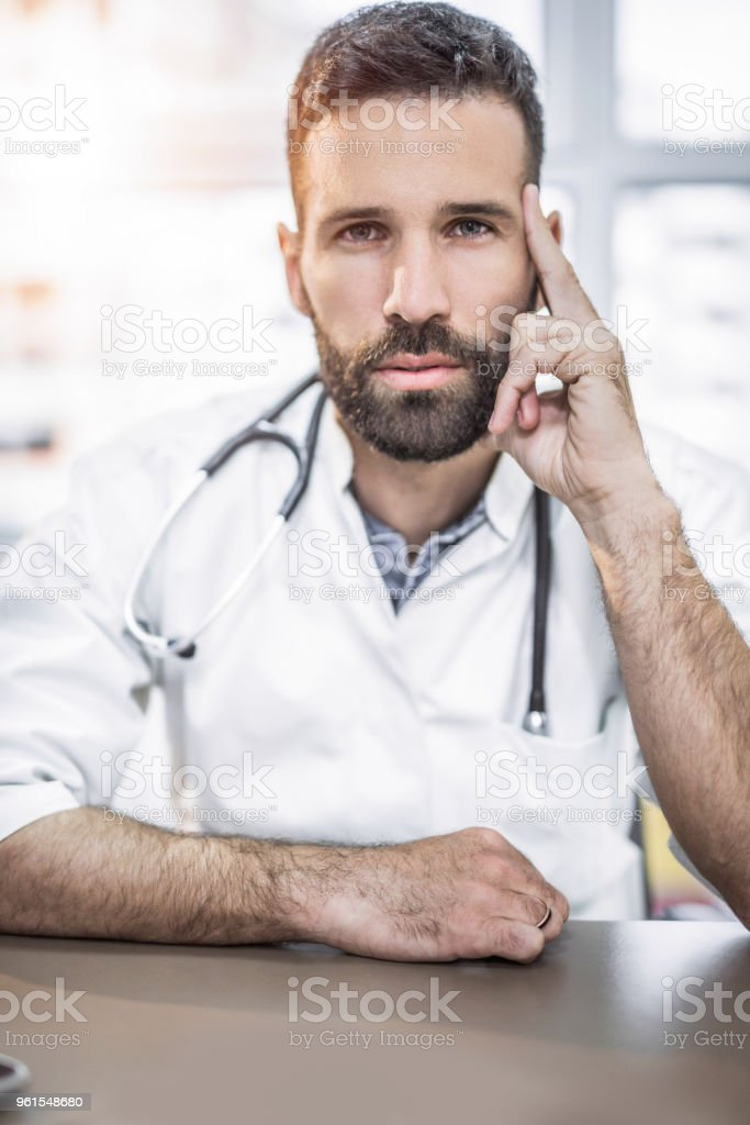 Handsome mid adult doctor contemplating and looking at camera. stock photo