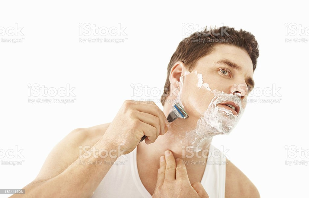 Handsome mid adult man using razor to shave beard royalty-free stock photo