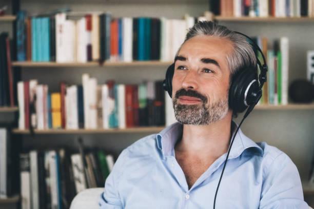 hübscher, mittlerer erwachsener Mann mit Kopfhörern, die die Musik genießen – Foto