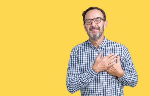 schöne mittelalter eleganten senior business mann mit brille über isolierte hintergrund mit händen auf brust mit geschlossenen augen und dankbar geste auf gesicht lächelnd. gesundheitskonzept. - die wahrheit tut weh stock-fotos und bilder
