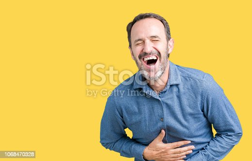 Handsome middle age elegant senior man over isolated background Smiling and laughing hard out loud because funny crazy joke. Happy expression.