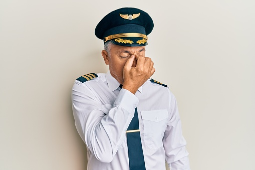 Handsome middle age mature man wearing airplane pilot uniform tired rubbing nose and eyes feeling fatigue and headache. stress and frustration concept.