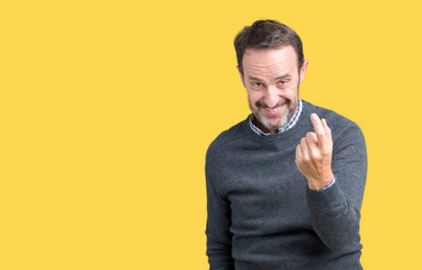 homem sênior bonito meia-idade, vestindo um suéter sobre fundo isolado acenando vir aqui gesto com a mão convidando feliz e sorridente - vem - fotografias e filmes do acervo